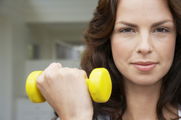 Woman lifting weight, head and shoulders