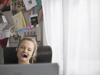 Woman using laptop wearing headset sitting at desk