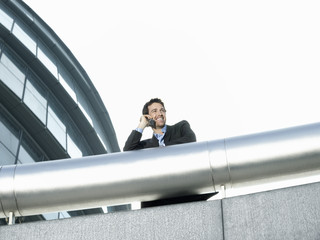 Businessman standing behind pipe outside office building, using mobile phone, low angle view