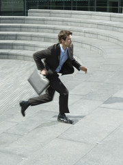 Businessman with briefcase running up steps outdoors, side view