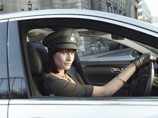 Female chauffeur in car on street