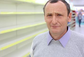 elderly man and empty shelves in  shop