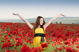 Smiling girl in the poppy field
