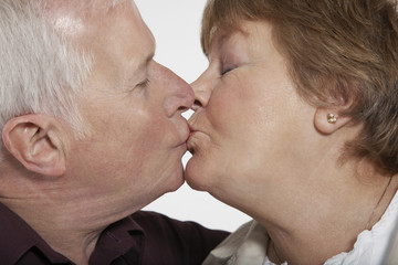 Profile of middle-aged couple kissing, close-up