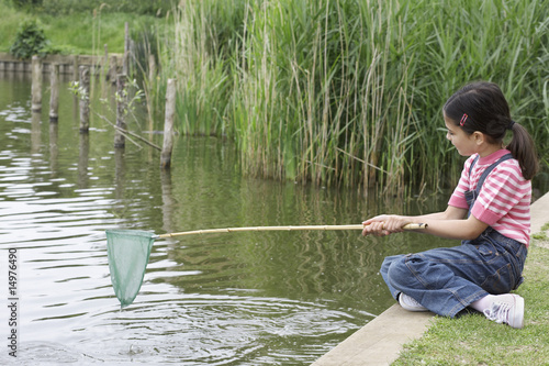 Girl 5-6 with fishing net at river