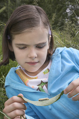 Girl 7-9 examining caterpillar on leaf in field