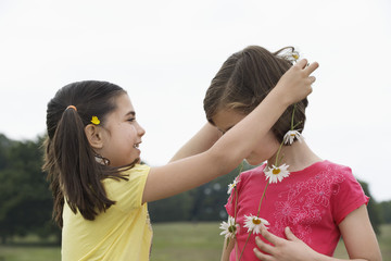 Girl 7-9 giving friend daisy chain in meadow