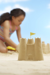 Girl 7-9 years building sand castles on beach, focus on sand castle in foreground