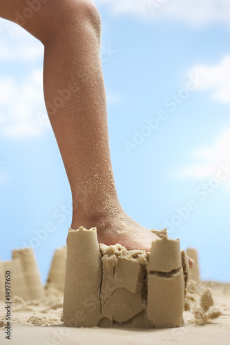Child stepping on sand castle, low section