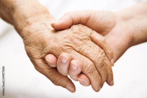Leinwanddruck Bild adult helping senior in hospital