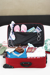 Open suitcase on bed, elevated view