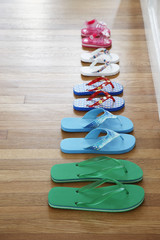 Row of flip-flops on floor, elevated view