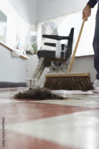 Barber sweeping floor in barber shop