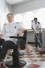 Two barbers in barber shop, one sweeping floor