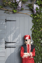 Portrait of young boy 7-9 in pirate costume by shed