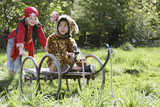 Portrait of boy 7-9 wearing pirate costume pushing boy 5-6 in cart in jaguar costume, garden