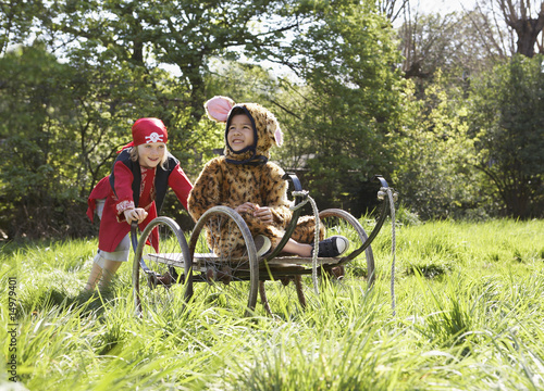 Young boy 7-9 in pirate costume pushing boy 5-6 in cart in jaguar costume, smiling