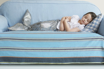 Young girl 5-6 wearing mermaid costume sleeping on sofa