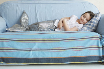 Portrait of young girl 5-6 lying on sofa in mermaid costume