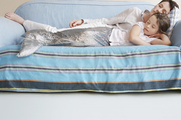 Young girl 5-6 wearing mermaid costume sleeping on sofa with mother