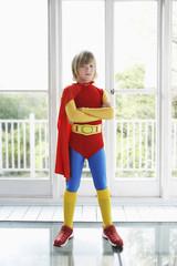 Portrait of young boy 7-9 in superhero costume, indoors