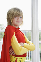 Portrait of boy 7-9 with arms crossed wearing superhero costume, smiling