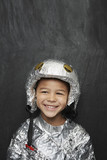 Portrait of young boy 5-6 in aluminum foil astronaut costume, smiling, studio shot