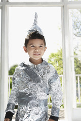 Portrait of young boy 5-6 wearing aluminum foil knight costume, indoors