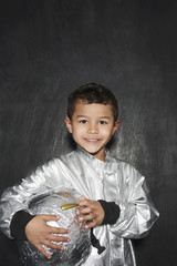 Portrait of young boy 5-6 in astronaut costume, holding helmet, smiling, studio shot
