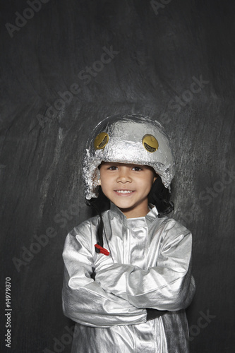 Portrait of young boy 5-6 in astronaut costume, crossed arms, smiling, studio shot