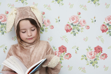 Young girl 5-6 n bunny costume reading book, wallpaper with floral pattern in background