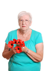 Senior woman holding fake red poppies