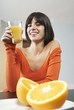 Woman holding glass with orange juice, portrait