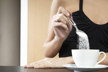 Woman pouring sugar into tea cup, mid section, close up