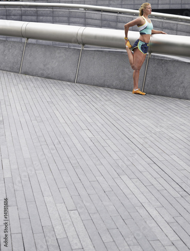 Female athlete stretching, outdoors, side view