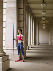 Female athlete holding javelin, standing in portico, portrait