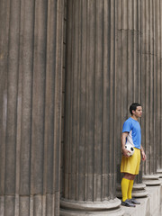 Soccer player holding ball, standing between columns, side view