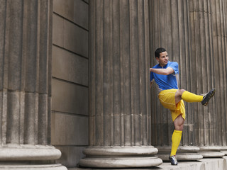 Soccer player kicking ball, standing between columns
