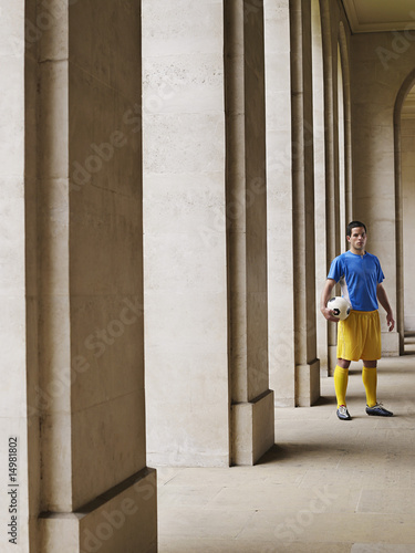 Soccer player holding ball, standing in portico, portrait