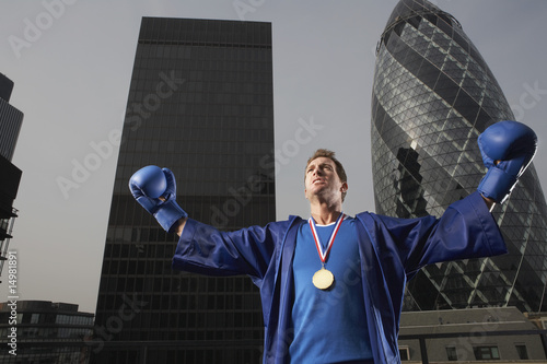 Boxer wearing gold medal standing in front of downtown skyscrapers, low angle view, London, England