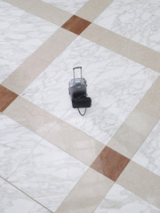 Suitcase and handbag on tiled floor, elevated view