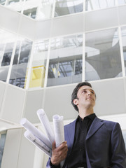 Business man holding rolled blueprints under arm in atrium of office building, low angle view