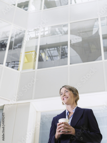 Business woman holding cup of coffee, standing in atrium of office building, low angle view
