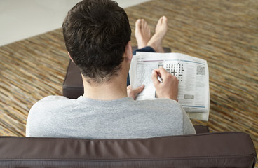 Young man sitting on sofa doing crossword puzzle in newspaper, back view