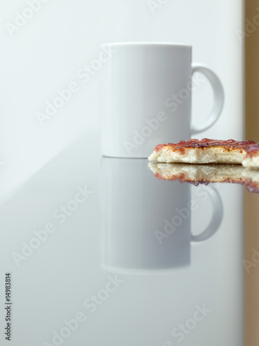 Cup and toast with jam on table, surface view
