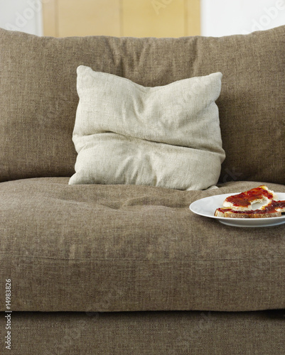Toast with jam on plate on sofa