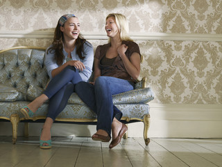 Two young women sitting on sofa, laughing