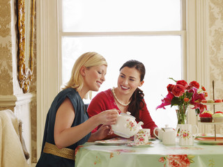 Two young women sitting at dining table, pouring tea