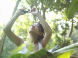Young woman in forest, taking photograph, arms raised
