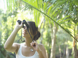 Young woman in tropical forest looking through binoculars